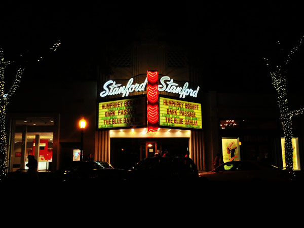 At night, the outside of the Stanford Theater illuminates Downtown Palo Alto.