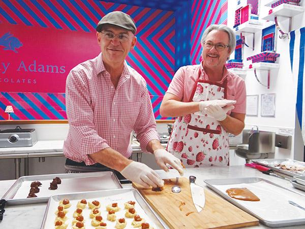 """Timothy Woods (left) and Adams Holland (right) roll caramel for their fresh bon-bons.  The two opened Timothy Adams Chocolates together just over two months ago.  """"There can be multiple dream jobs in life, but, yeah, this is one of them,"""" Woods says."""