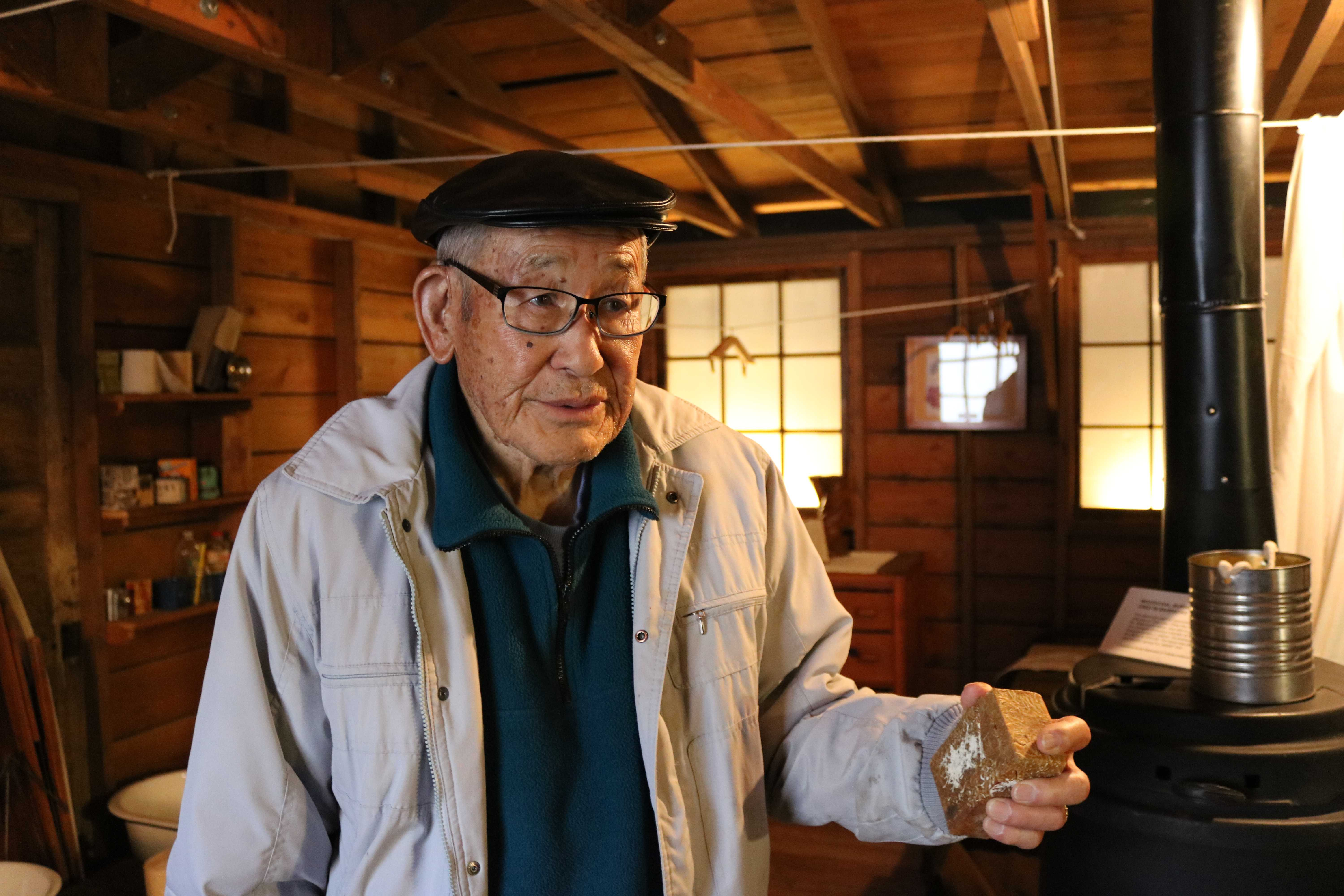 Jimi Yamaichi holds a brick that he brought back from Tule Lake inside a recreation of the barracks at the Japanese-American Museum of San Jose. Click to read his story. Photo by Gabriela Rossner.