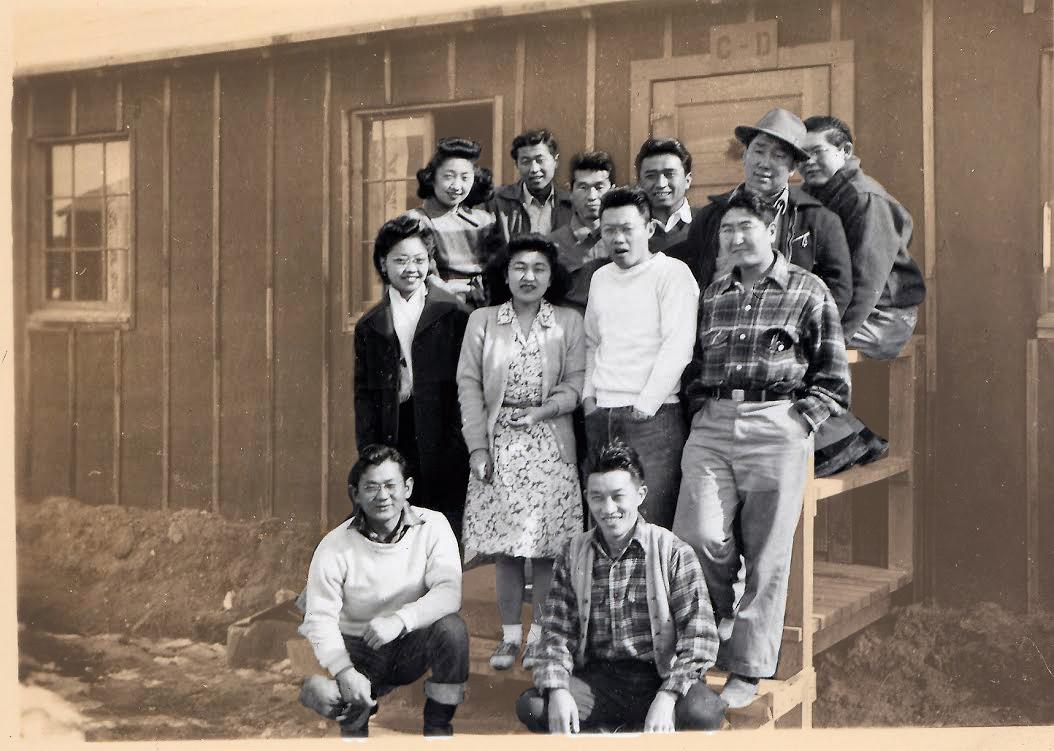 "Palo Alto Japanese-Americans in front of their barracks at Heart Mountain. Back: Kiyo, Fred, Tad Tani, Frank Shimada, Henry ""Hammy"" Hamasaki, Saku Taketa Front: Riyo, Mary, Jack,, Eldan Kneeling: Ben Kamada, Frank Furuichi"