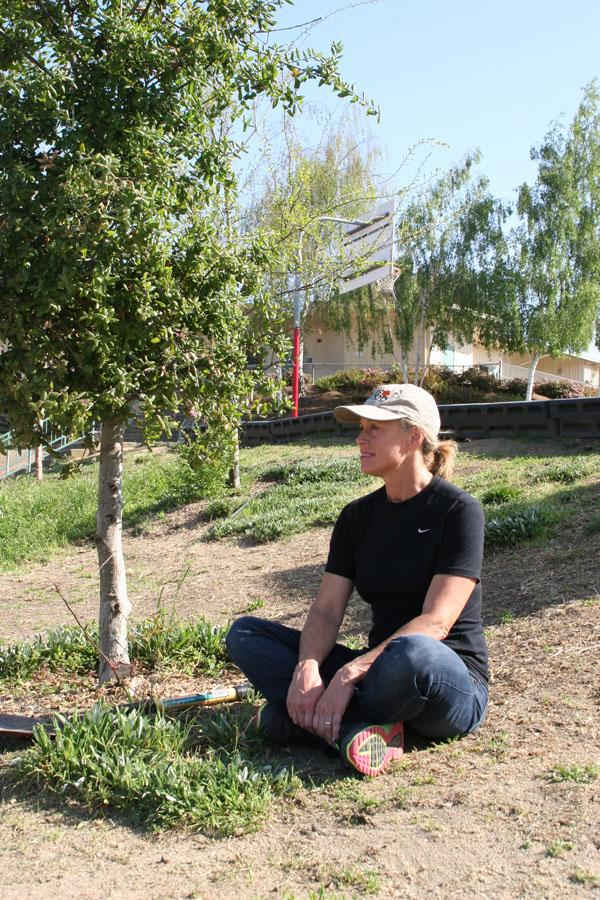 Canopy volunteer Carole Langston by a tree planted by Canopy at Nixon Elementary School in Palo Alto several years ago.