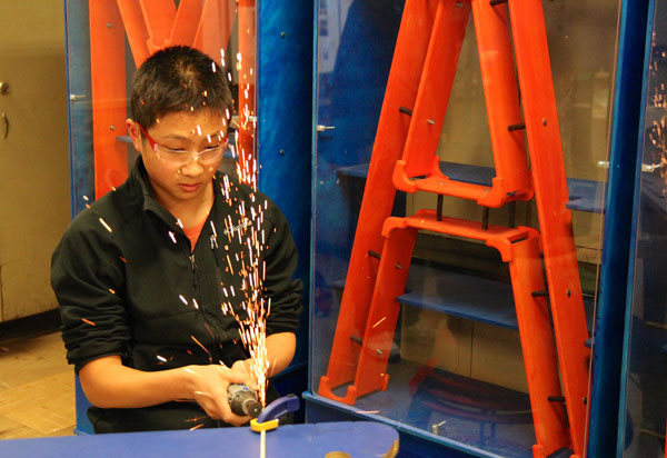 James Wang generate sparks as he cuts metal screws.