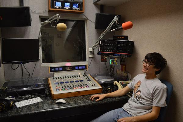Sophomore Kai Gallagher sits in a KZSU radio studio.