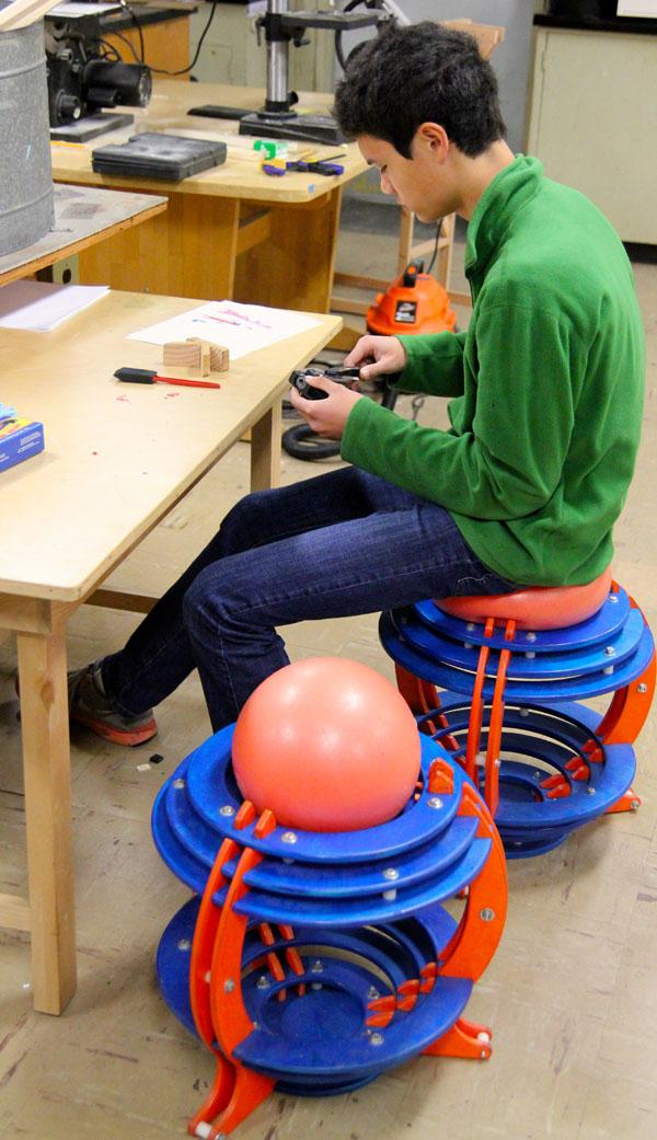 Nathan Kau works upon a chair designed by the Make X design team.