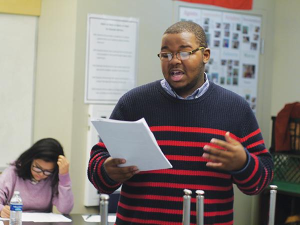 Jacob Adams reads from a prepared sheet while debating at Eastside College Prep.