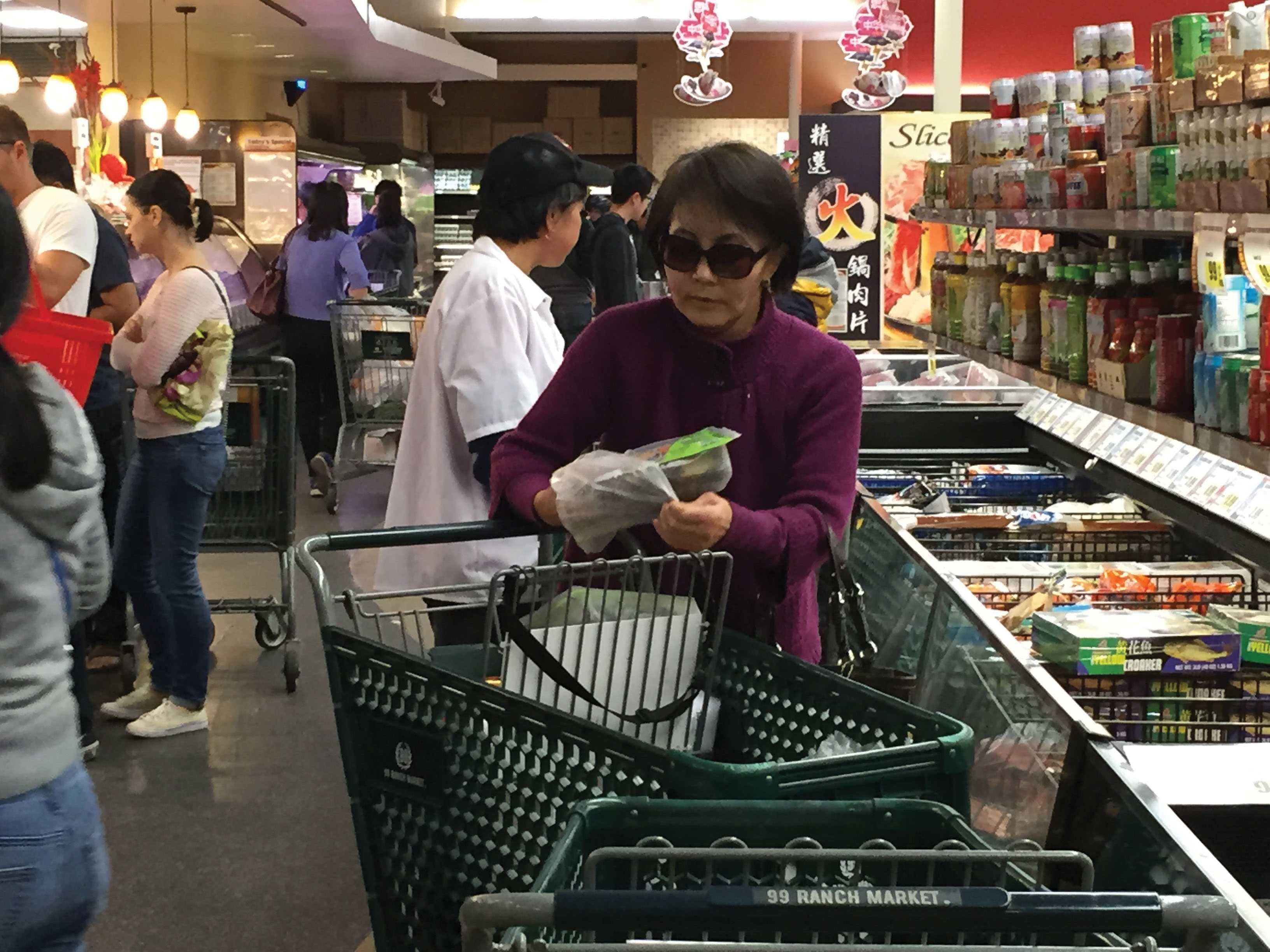 After carefully examining the meat selection, a shopper chooses rib eye.