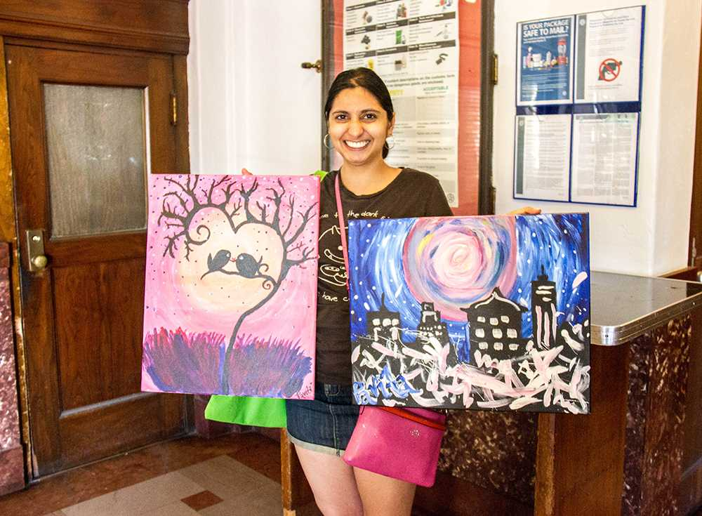 Singh holds her paintings, which will be sent to friends living on the East Coast