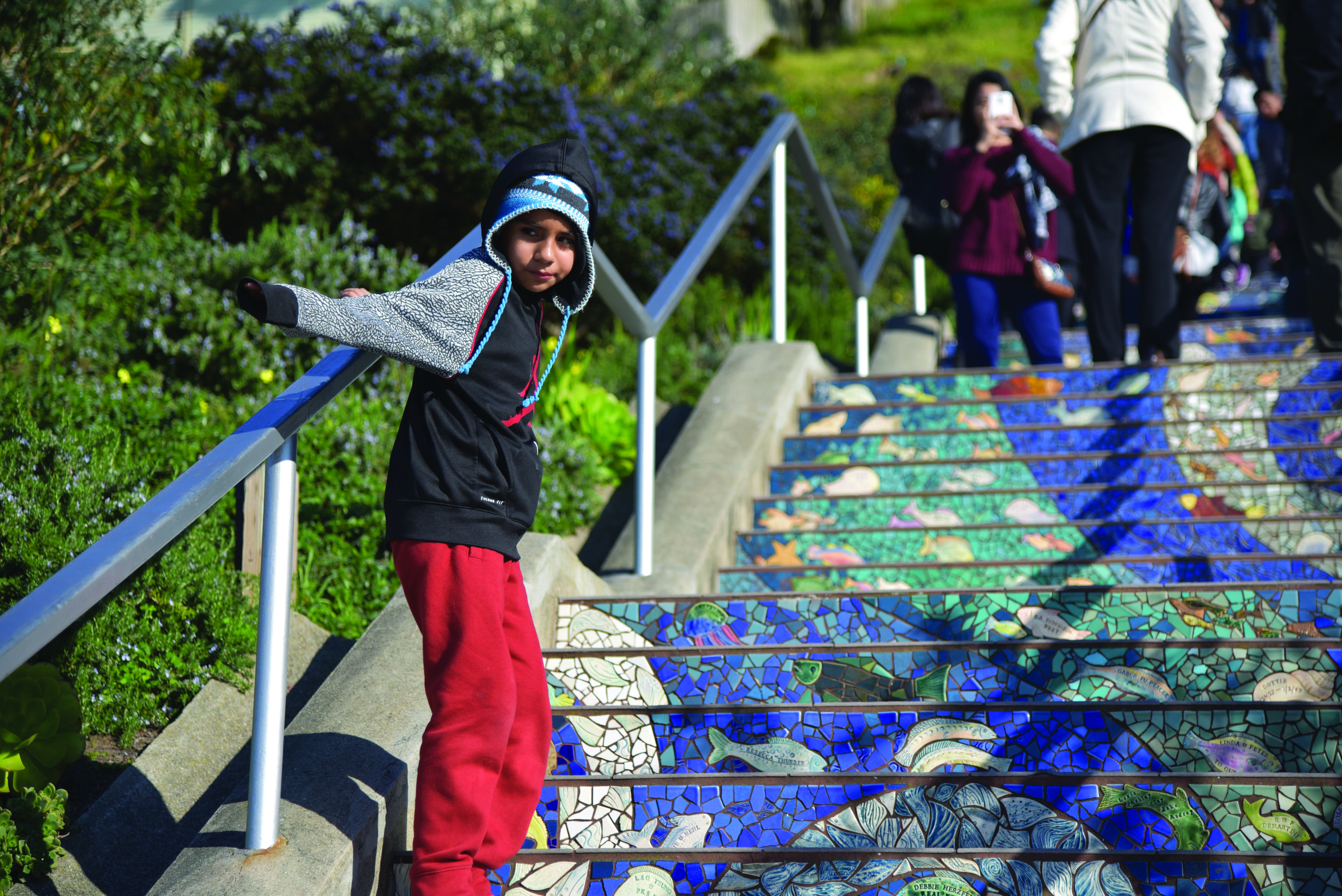 A boy slides along the handrail of the 16th Ave Tiled Steps, a popular destination for locals and tourists.