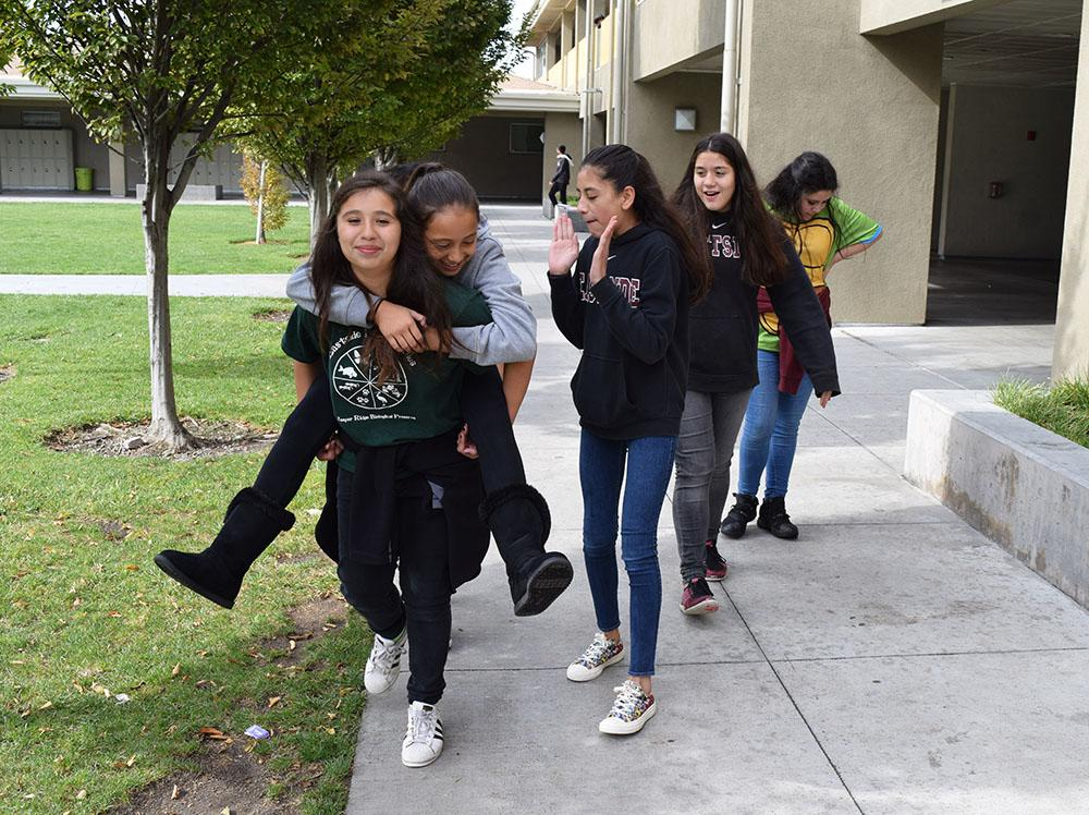 """PIGGY BACK RIDE Middle schoolers at Eastside relax during their lunch break on a crisp day. """"My favorite thing about Eastside is that it makes us feel like a family,"""" one student says. The first generation students, many of whom live on campus, enjoy the benefits of a modern private school education. Photo by Alicia Mies."""